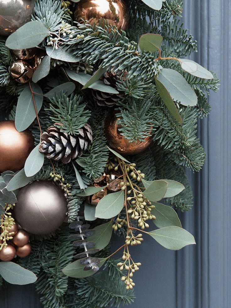 Handmade exclusively for Cox & Cox by luxury artisan florist Flowers By Passion, our Christmas wreaths are crafted using a sumptuous array of seasonal foliage, beautiful copper and grey baubles, frosted pine cones and miniature copper bells. The perfect centrepiece for your front door, each unique wreath has been made on a mossed ring frame and includes a mix of preserved eucalyptus in green-blue tones, scented blue pine that evokes the scent of Christmas, pine cones and shatterproof baubles…