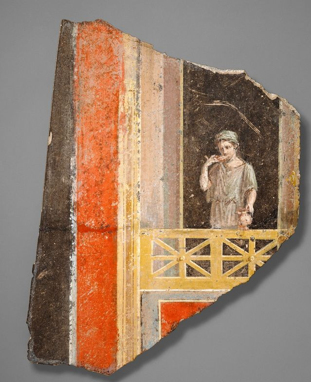 """Wall Fragment with a Woman on a Balcony, about 9 B.C.- A.D. 14, The J. Paul Getty Museum. Pompeian red was named after the excavations at Pompeii, Italy. However, this red is actually a dehydrated form of yellow ocher. That is to say, these frescoes were most likely yellow during their creation, and only after extreme heat application (perhaps from a volcanic eruption) did the yellow become the ever-so-popular """"Pompeian red."""""""