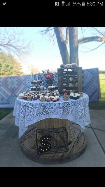 Wedding cake/cupcake display.  Rustic spool table. Lace. Crates. Quilts.