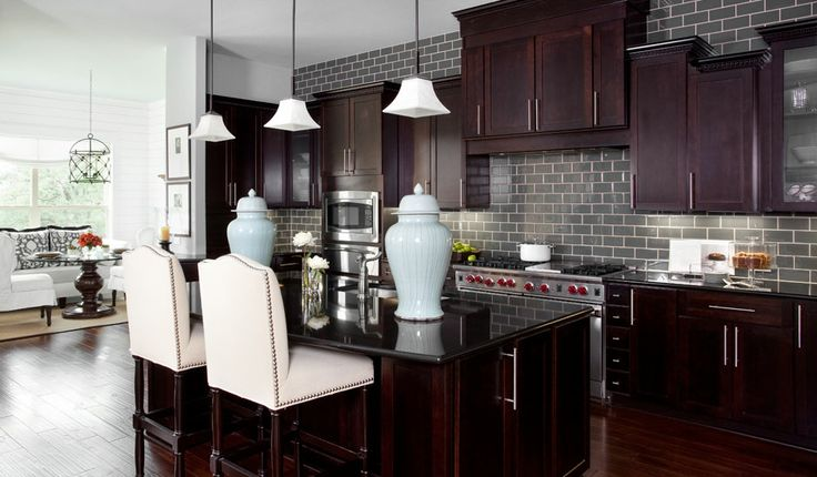 modern traditional   gray subway tile + dark wood cabinets + cabinet uppers of various heights + cabinet hardware