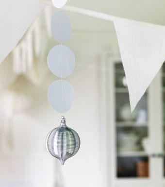 A close-up of silver and white paper Christmas decorations hanging from a ceiling.