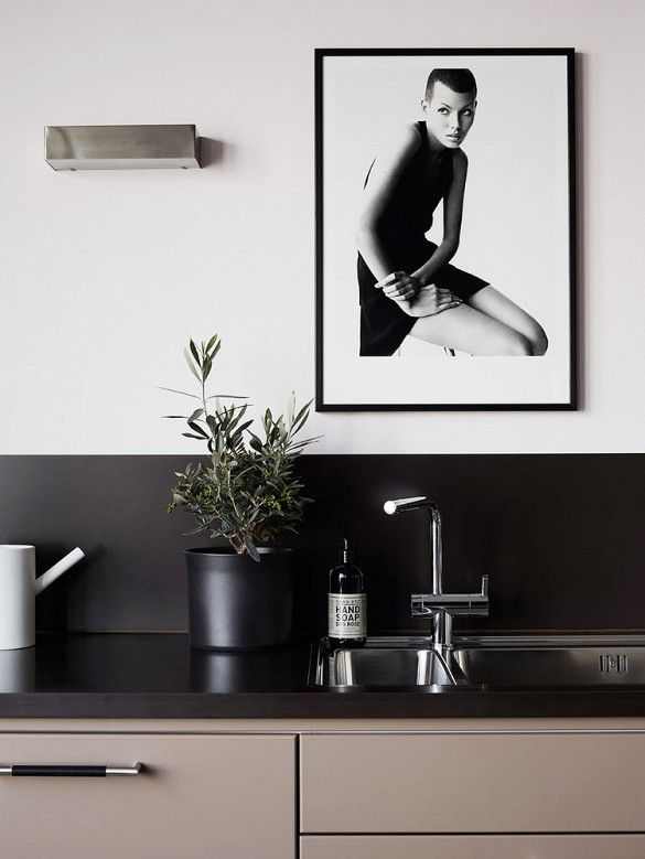Sleek grey kitchen with black granite counter tops and a black and white framed print