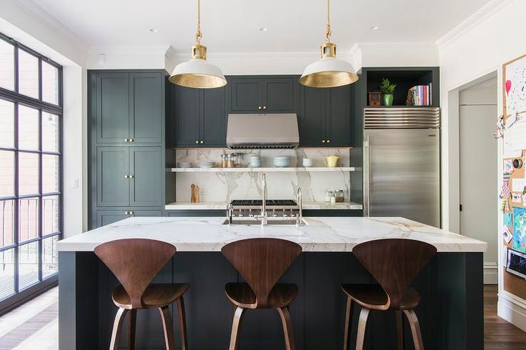 Contemporary gray black and white kitchen is furnished with Cherner Counter Stools seated in front of a gray black island topped with white marble countertops fitted with an undermount sink with a polished nickel gooseneck faucet illuminated by white and gold pendants.