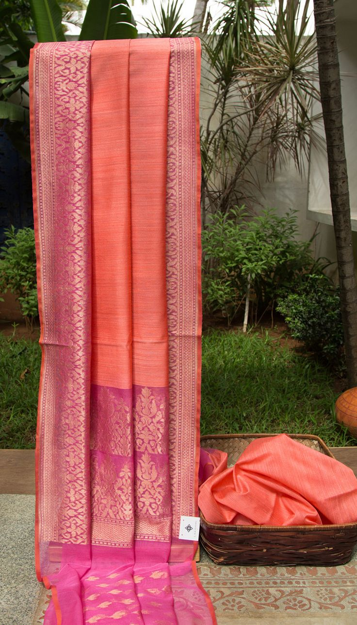 This stunning coral toned benares net sari comes with a detailed gold zari work that runs in the fuchsia pink colored border and extends into the pallu as well. The selvedge is in a contrasting str…