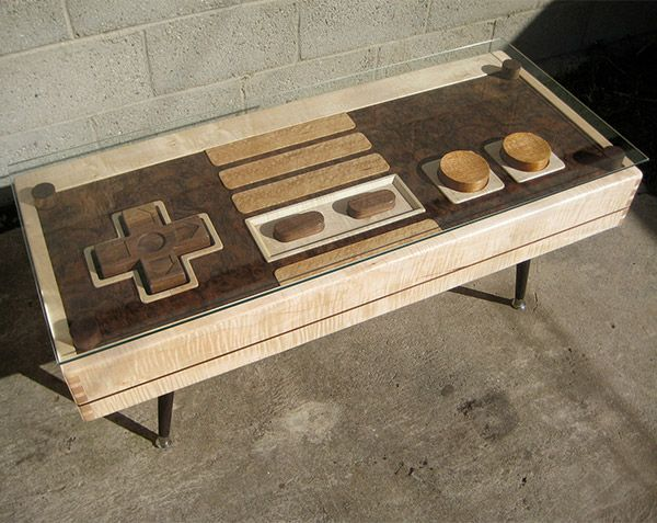 """It's made by The Bohemian Workbench, using maple, mahogany, and walnut with dovetail joinery, so it not only looks good. Just remove the glass and it actually plays games when you hook it up to an old NES. It is built with quality as well. This table means serious business. It's about 42″ long by 18.25″ wide, and stands at about 18"""" tall. It also will cost you $3,500(USD), plus shipping"""