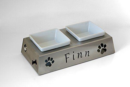 Aus der Kategorie Hundebars & Napfständer   gibt es, zum Preis von   Es handelt sich hierbei um eine hochwertige Futter- und Trinkbar. Diese ist für Hunde und Katzen geeignet. Die beiden Näpfe sind aus robusten Keramik. Das Blechmaterial des Napfhalters besteht aus 1,5mm dicken, geschliffenem Edelstahl. Natürlich Rostfrei. Auf der Unterseite befinden sich Gummistellfüsse, damit der Napf problemlos abgestellt werden kann, ohne Kratzspuren zu hinterlassen. Der Name wird individuell durch das…