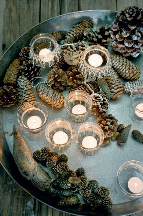 candles in a metal tray with found nature objects - pinecones and such