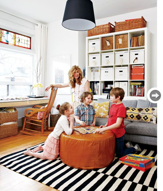Beautifully balanced, a striped black and white rug pulls it all together.  color schemes black white beige brown orange gold wood shelving