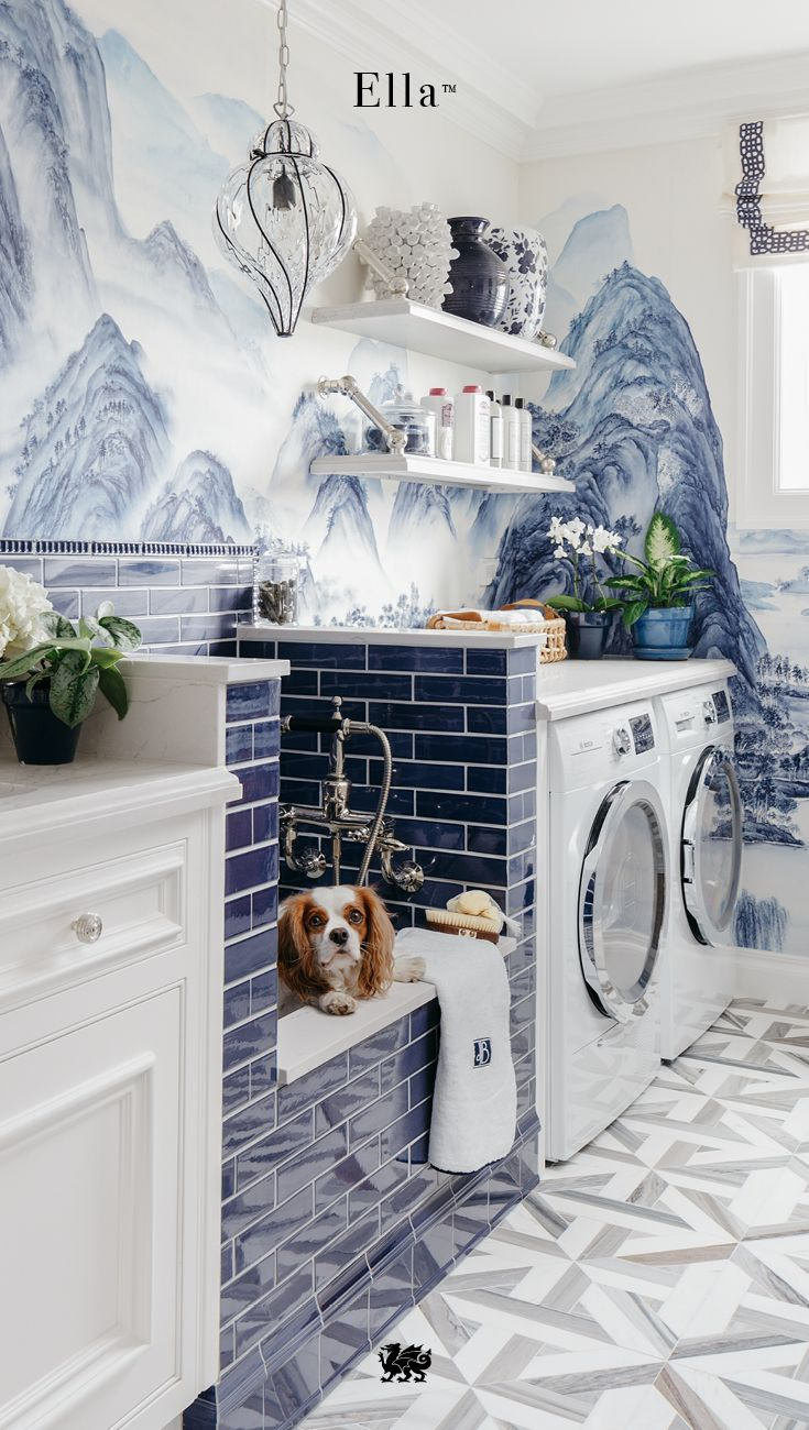 This luxurious pet-friendly home has a dog wash station in the laundry room. Cambria Ella™ keeps the space low maintenance and easy to clean. Degournay wallpaper, cobalt subway tile, and this elegant quartz countertop design make time spent doing laundry anything but a chore. Multiple uses of Cambria Ella™, including a deep sink surround, shelving, and folding station atop the washer and dryer, show the versatility of this nonporous, natural stone surface.