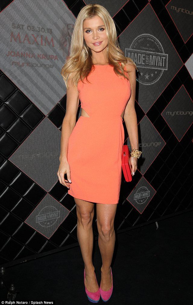 Colour clash: The model wears pink and blue heels with a peach cutaway dress and red clutch bag
