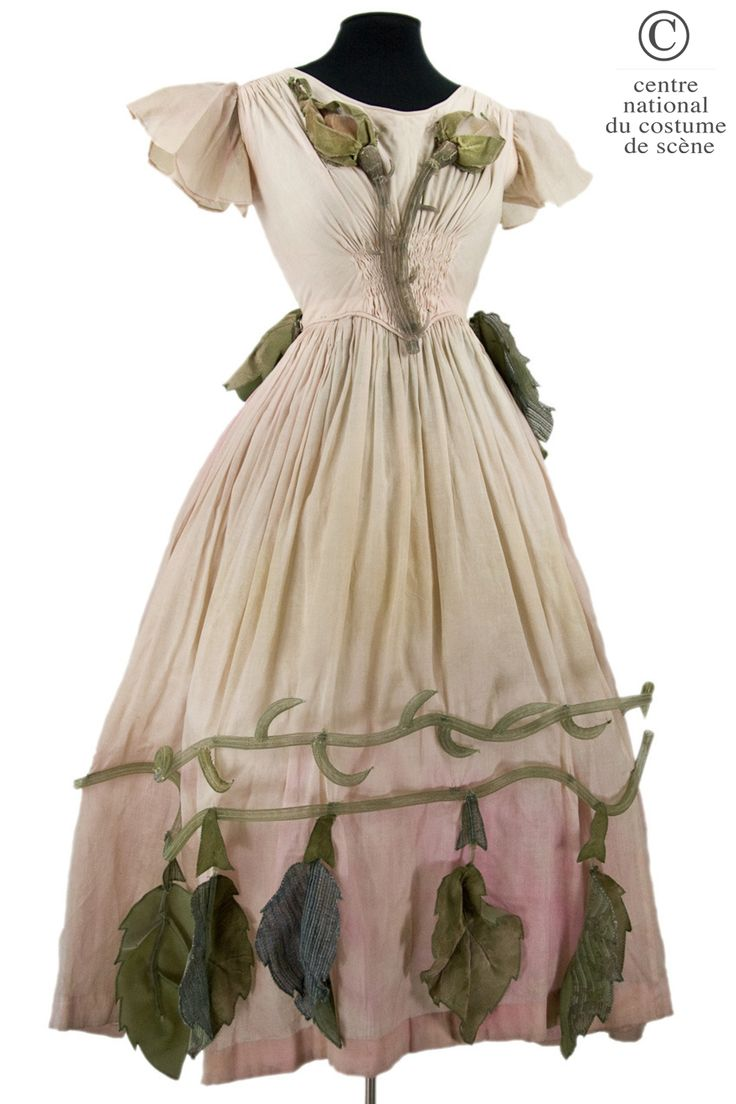 A flower 1977. DESIGNER: Emilio Carcano. COSTUME DESCRIPTION:  Long dress in cotton dyed pink, trimmed with ornaments textile applications, painted hair green leaves and sisal. Gathers on the shoulder line and loose sleeves. Front: