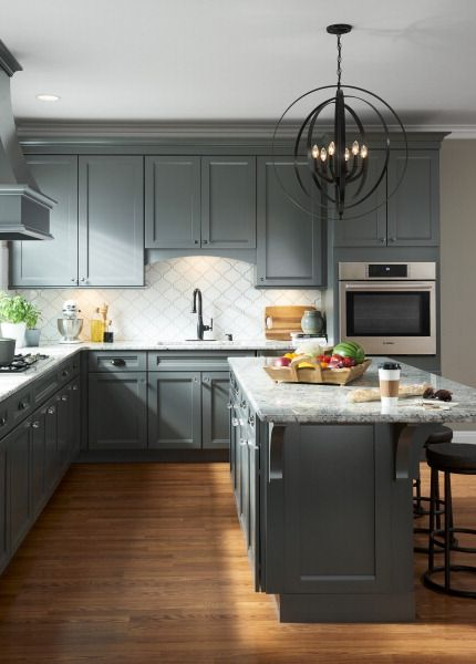 Gray neutrals and stainless steel appliances create a stunning kitchen style. An oversize bronze chandelier shines as a bold focal point. Let a Lowe's designer help you create your dream design - click to get started.
