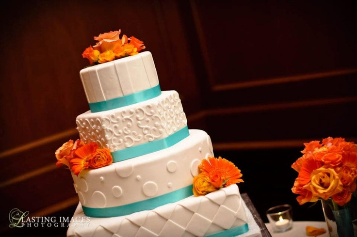 Tall four-tier wedding cake separated by orange roses; Tiffany blue ribbon bands and white polka dot piping | Marriott Photography | villasiena.cc