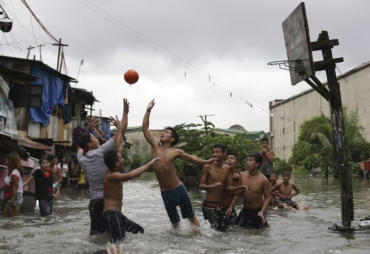 Filipino boys play basketball in floodwater from a swollen creek at a coastal village in Malabon, north of Manila, Philippines, on July 8, 2015. Typhoon Chan-Hom, which passed over the northeastern waters of the Philippines on its way to northern Taiwan, enhanced the seasonal monsoon, dumping heavy rains over the capital, Manila, and the northern provinces.