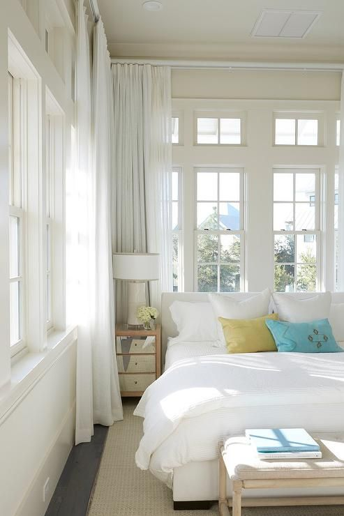 Beach style bedroom is filled with a white upholstered bed dressed in green and blue velvet pillows placed next to a small mirrored nightstand and a cream lamp placed in front of a wall of windows dressed in white curtains.
