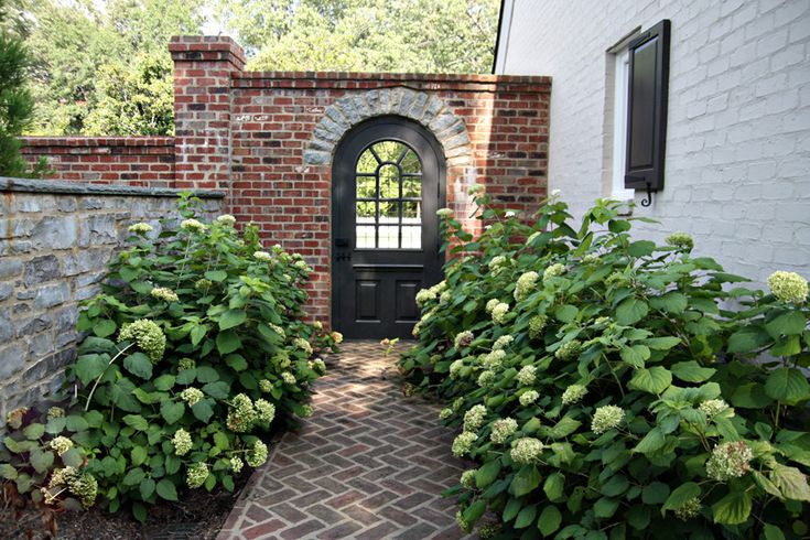This image is from the Urban Grace blog.  Painted brick house with brick fence, lovely rounded door entry into garden of hydrangea.  Like they plucked it straight from my dreams......