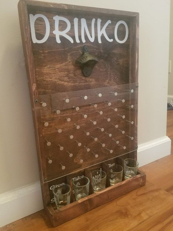 Add a little fun and whimsy with the drinking version of the game Plinko. This will be a great addition to your bar, game room, or man cave!  Item pictured is finished with walnut stain and rustic bottle opener but also available in an oak, mahogany and ebony finish. Chrome bottle opener also available. Choose your stain and opener preference during checkout. Made with durable plexiglass and measures approximately 21 X 13.  Two styles available: Without bottle cap tray With bottle cap tray…