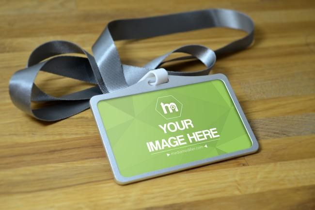 A blank lanyard name tag holder on a wood table background. Online mockup generator for a name tag design.
