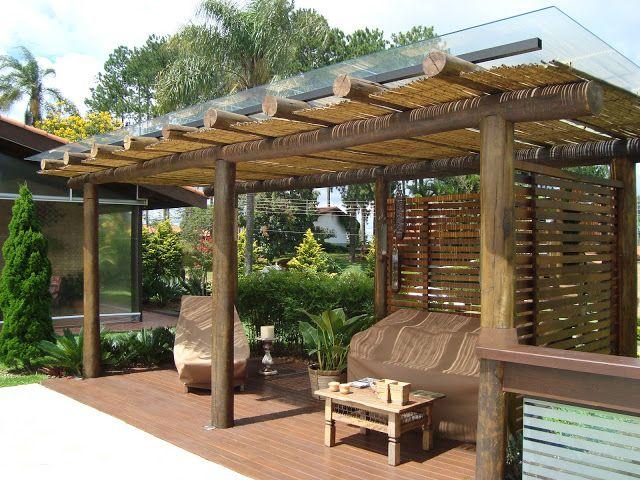 Nessa varanda, bem maior, o pergolado feito com madeira roliça dá um ar bem mais rútico, apesar da cobertura de vidro