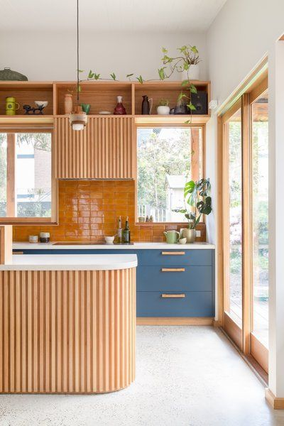 Mar 3, 2020 - Shielded by overhanging eaves, ample northern glazing lets in an abundance of natural light and views of the outdoors. Tagged: Kitchen, Ceramic Tile Backsplashe, Wood Cabinet, Engineered Quartz Counter, Concrete Floor, Pendant Lighting, Cooktops, and Colorful Cabinet.