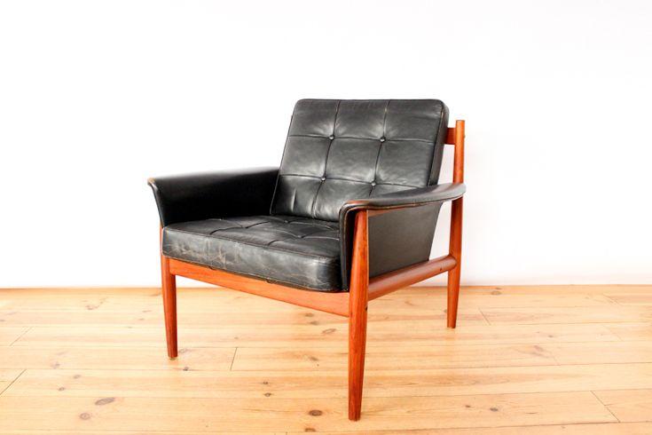 Fauteuil modèle '118' structure en teck, assise en cuir noir (d'origine)  Designer: Grete Jalk (Danemark) Editeur: France & Son  Dimensions: Largeur 82cm / Profondeur 77cm / Hauteur d'assise 43cm / Hauteur 76cm