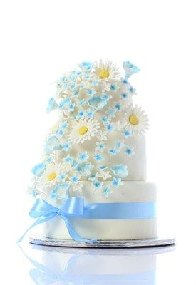 A beautiful white wedding cake with blue flowers and daisy's to give it a real summer feel