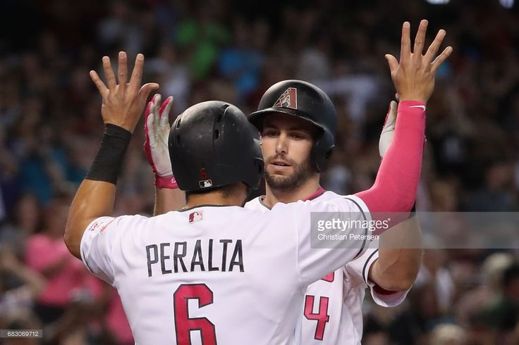 Paul Goldschmidt #44 of the Arizona Diamondbacks high fives David Peralta #6 after hitting a two run home run against the Pittsburgh Pirates during the first inning of the MLB game at Chase Field on May 14, 2017 in Phoenix, Arizona. Players are wearing pink to celebrate Mother's Day weekend and support breast cancer awareness.