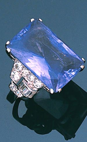 An art deco sapphire and diamond ring, circa 1935 Claw-set with a step-cut sapphire, weighing 31.64 carats, between brilliant and baguette-cut diamond geometric shoulders, ring size M½
