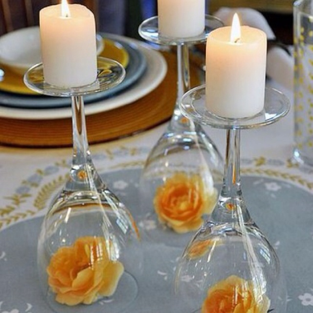 Flowers underneath an upside down wine glass used as a pillar for candles makes a beautiful centerpiece.