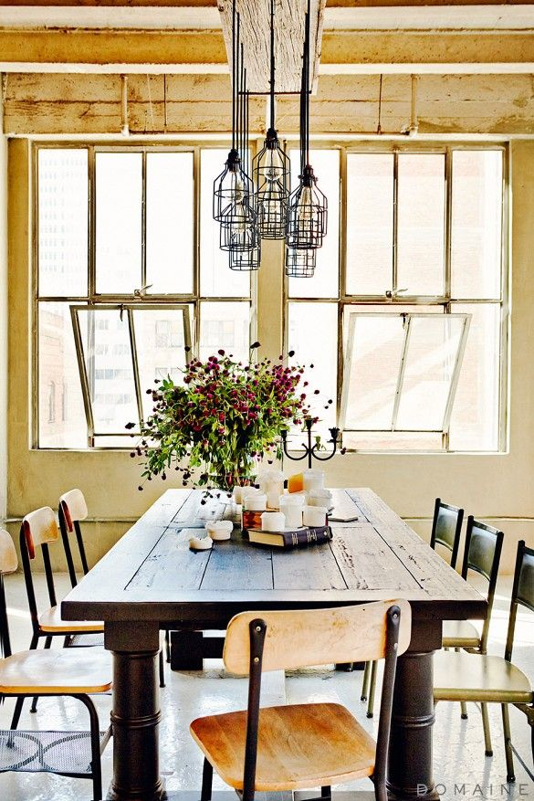 Rustic dining table and Edison bulb chandelier and candle arrangement in loft apartment.
