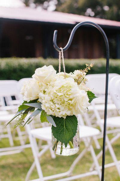 Simple boho chic wedding ceremony aisle marker idea - white hydrangeas + ivory roses + greenery in jars {Riverland Studios}