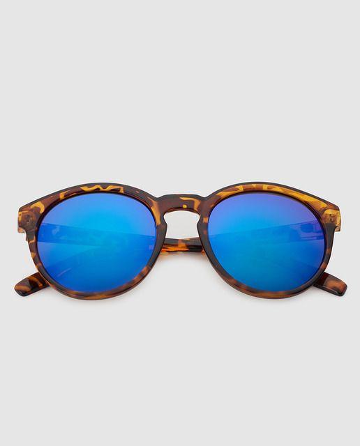 Gafas redondas de color miel, las lentes son de color gris.