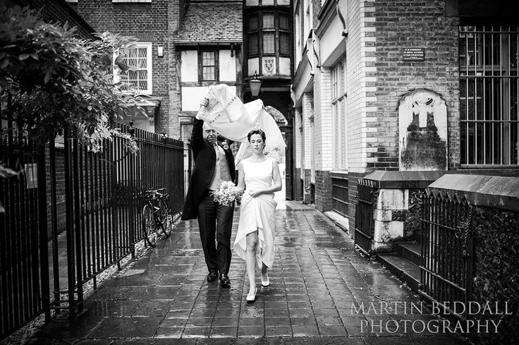 Brides father tries to keep the rain off her