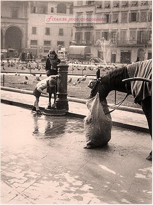 Bello scorcio di Piazza Santa Maria Novella con un bimbo che beve alla fontana e una donna, anni 60 #Firenze.