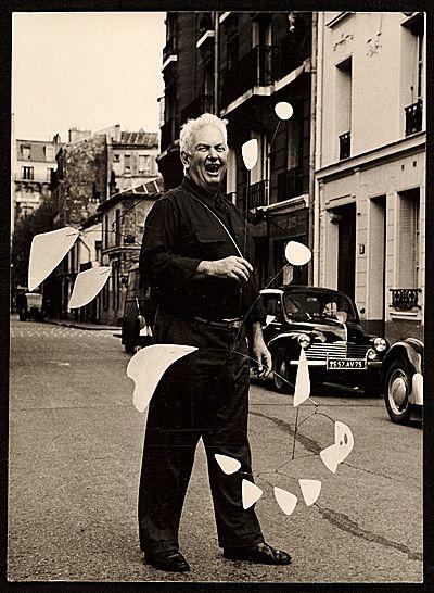Alexander Calder holding his mobile on a Parisian street, 1954