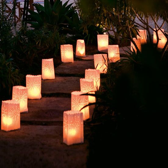 Paper luminaries  Lighting has a huge impact on the atmosphere of a party, so line the entrance route with paper luminaries to create a lovely warm glow as guests arrive.  You can either fill these with a little sand and pop a jam jar with a votive candle inside or, if you want to be really safe, use a battery powered LED candle with a flickering flame effect or one of the special base holders below.