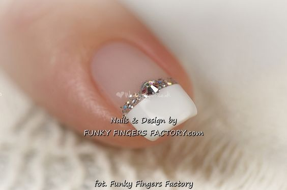 Lovely, serene, with just a hint of spice and glam this nail art is perferct for a wedding or a prom. Funky Fingers Factory has highlighted the traditional French manicure then highlights the nail tip with rhinestones and Glitter. - See more at: https://www.dailynails.com/nail-art?f[0]=field_theme:216#.dpuf