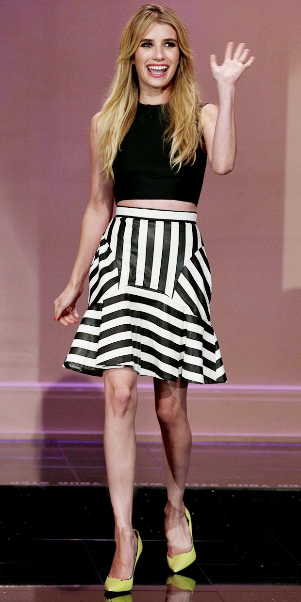 Emma Roberts looking cute as ever in a cropped black top and a jailhouse stripe skirt with bold Jimmy Choo heels.