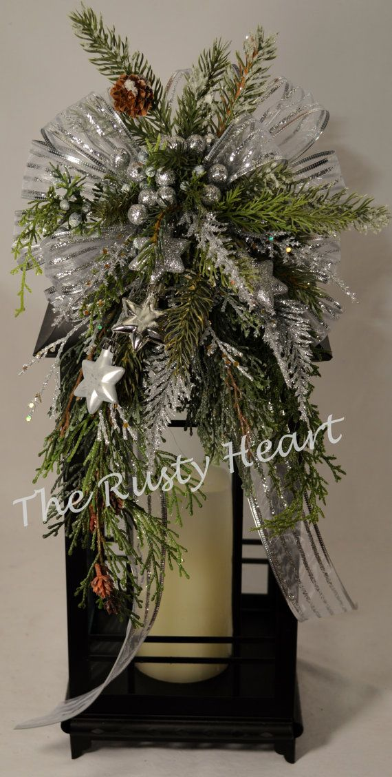 Our lantern swags are great way dress up any lantern! This swag is decorated with silver shear ribbon, various greens, snowy pine, silver stars,