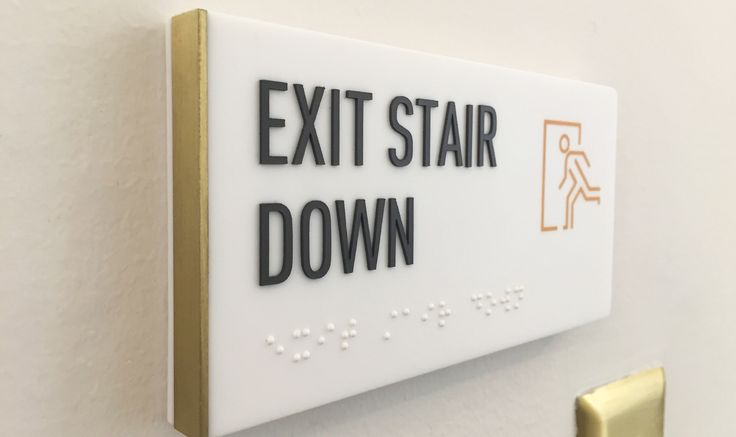 Egress ADA Sign Custom solid surface material with inset brass edge detail.  251 Post Office Building, San Francisco, California — 505Design – Environmental Graphics