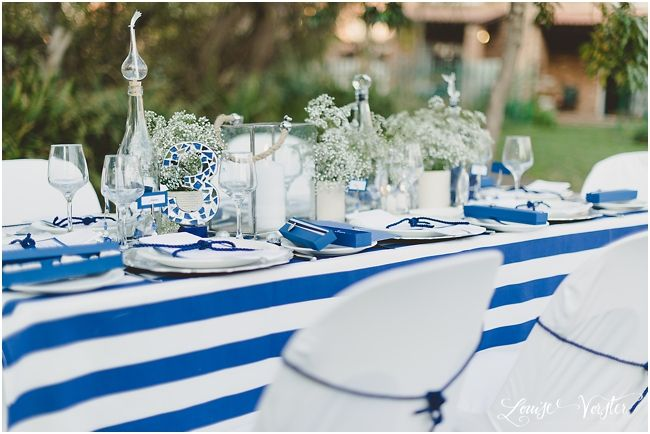 View of blue and white table cloth with white chair covers and blue rope chair ties.