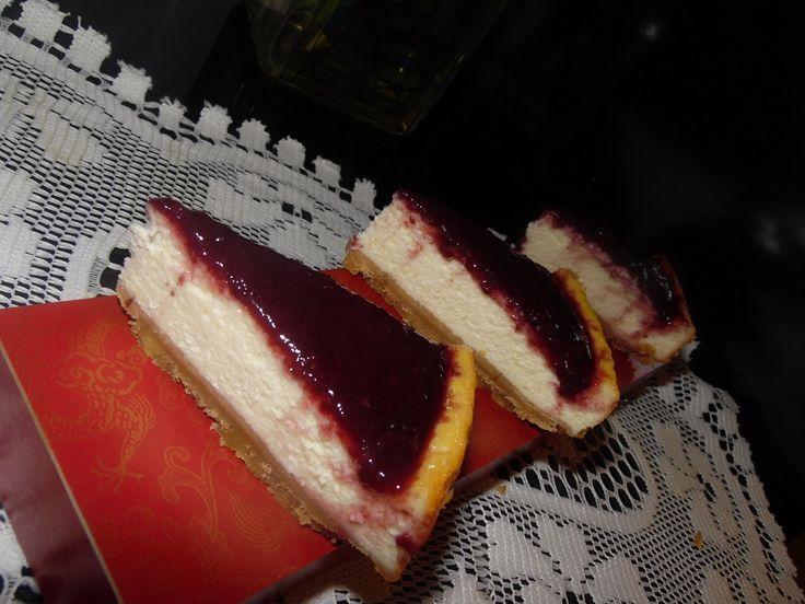Ricetta di una cheesecake classica mascarpone e formaggio spalmabile, cotta in forno, con copertura di glassa alla marmellata di ciliegie.