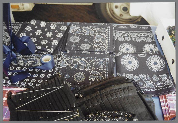 Streekdrachtstoffen op marktkraam van Booy uit Zwartsluis, gefotografeerd op weekmarkt te Staphorst. Op blauwe zeil verschillende schouderdoeken, hoofddoeken en rokken. Vooraan verschillende schouderdoeken voor niet-rouw (met rood) en lichte of zware rouw (zwart/blauw) Daarbovenop 2 onderrokken voor zware rouw, plooien vastgeregen met rijgsteek. Daarachter hoofddoeken met verschillende motieven. Daarbovenop ligt rolletje blauw satijn lint voor kerkschortbanden. 2002 #Overijssel #Staphorst