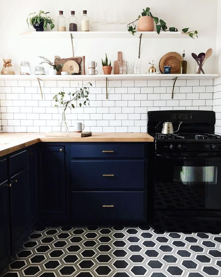 Compact kitchen renovation with brass drawer pulls, white subway tile backsplash, geometric patterned black and white honeycomb hexagon tiles and DIY open shelves