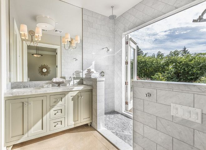 This stunning bathroom features a unique shower with rock flooring and French doors to a private garden.