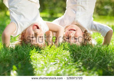 Happy children playing head over heels on green grass in spring park - stock photo