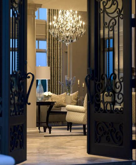 The dramatic iron doors enter into a expanxive foyer that for Entryway into living room ideas