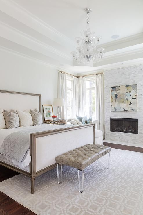 Chic bedroom features a white and taupe French bed draped with a gray silk quilt placed next to a mirrored nightstand placed atop a taupe geometric rug, A clear glass tiered chandelier illuminates a taupe leather tufted bench placed at the foot of the bed placed directly across from a white mosaic marble tiled fireplace lined with an abstract art piece.