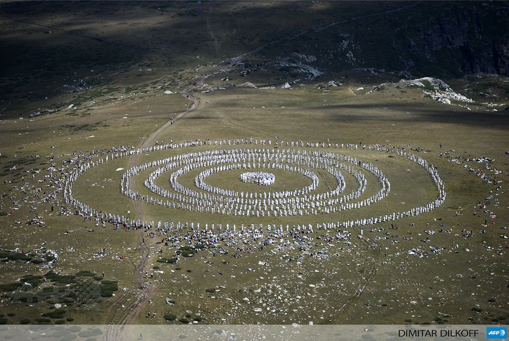 BULGARIA, SEVEN RILA LAKES: Members of an international religious movement called the White Brotherhood perform ritual dances on the top of the Rila Mountain, near Babreka lake, on August 19, 2013. The teaching of the movement, whose founder is Bulgarian Peter Deunov, combines aspects of Christianity and Hinduism with a heavy emphasis on brotherly love, a healthy diet and living in harmony with nature. AFP PHOTO / DIMITAR DILKOFF