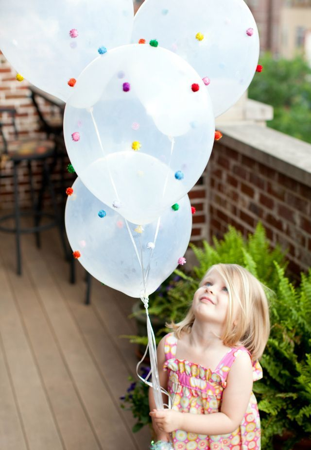 These whimsical and colorful pom pom balloons are perfect for a gumball birthday party! Materials needed: clear balloons, pom poms, and hot glue.